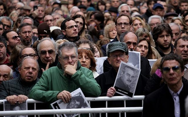 People hold up pictures of victims at a commemoration ceremony 25 years after the terrorist attack on the Jewish community's AMIA building in Buenos Aires, July 18, 2019. (Carol Smiljan/NurPhoto/Getty Images)