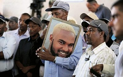 Family members and friends hold a picture of Solomon Teka during his funeral. Photo: EPA/Abir Sultan