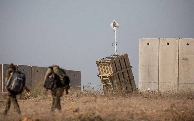Israeli soldiers walk near an Iron Dome anti-missile battery in the southern Israeli city of Sderot, Aug. 9, 2018. (Yonatan Sindel/Flash90)