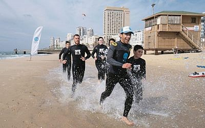 Ha'Gal Sheli co-founder Yaron Waksman (front) leading a surfing lesson for at-risk teenagers in Tel Aviv.