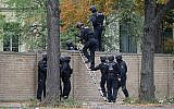 Police officers cross a wall at a crime scene in Halle, Germany, Oct. 9, 2019 after a shooting incident. (Sebastian Willnow/dpa via AP)