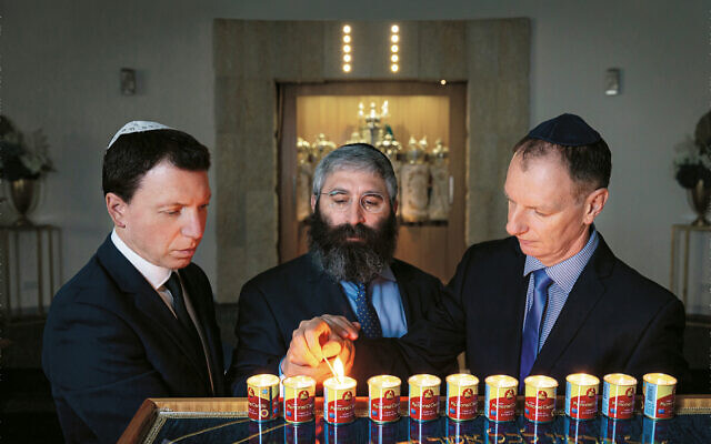 From left: Dvir Abramovich, Rabbi Motty Liberow and David Southwick light candles for the victims of the Tree of Life synagogue tragedy.