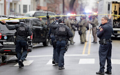 Police officers gather near the scene of a shooting, December 10, 2019, in Jersey City, New Jersey. (AP Photo/Seth Wenig)