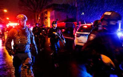 Law enforcement personnel walk near the scene of a shooting in Jersey City, New Jersey, Dec. 10, 2019. (AP Photo/Eduardo Munoz Alvarez)