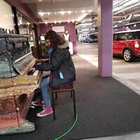 Amanda Morris plays piano for 'Mini' car day in the Melbourne Arts Centre carpark.