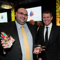 Joshua Levi with the multiple trophies he won at the NSW Premier's Multicultural Media Awards in 2016, alongside then-premier Mike Baird.
