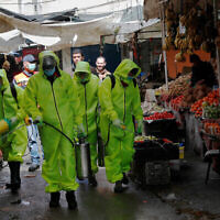 Workers in protective gear spray disinfectant at the main market in Gaza City on March 27. Photo: AP/Adel Hana