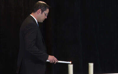 Rav Yehoshua Asulin lighting a candle in memory of his two uncles killed on IDF duty.