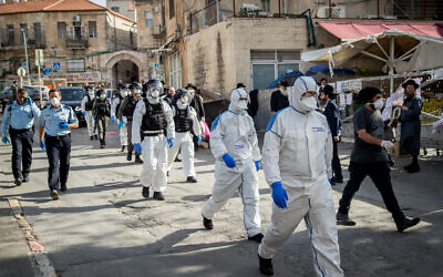 Israeli police officers wearing protective clothing as a preventive measure against the coronavirus in the religious neighbourhood of Mea Shearim, April 6, 2020. (Yonatan Sindel/Flash90)