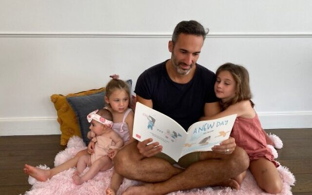 Lilah, Elly and Maya enjoy reading A New Day – written by their father, Sydney's Alex Ryvchin.