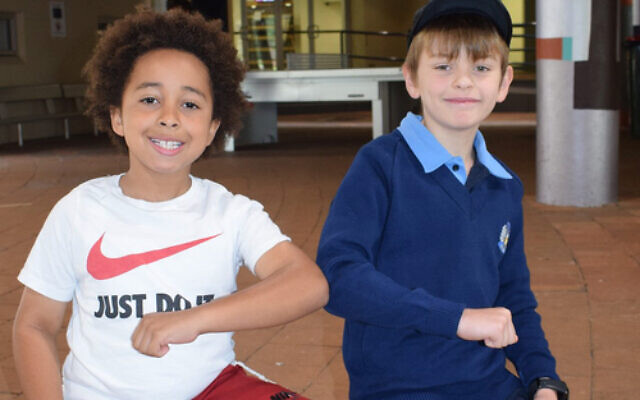 Elbow exchange: Masada College primary students Izaac Wyzenbeek (left) and Aleksay Berry were happy to return to school last week. Normal classes begin resuming on Monday.