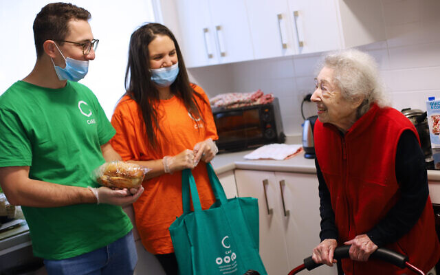 C Care volunteers Jeremy Sher and Taryn Abrahams deliver a C Care Shabbat pack to 98-year-old Rose Sugarman. Photo: Peter Haskin