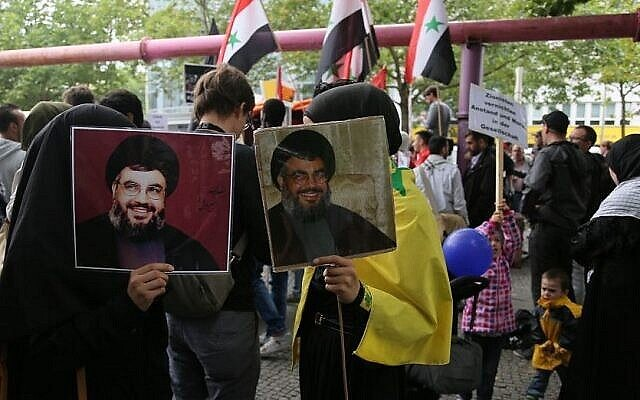 Protesters hold photos of Hezbollah chief Hassan Nasrallah at Al Quds day demonstration in Berlin, July 25, 2014. (Photo credit: Micki Weinberg)