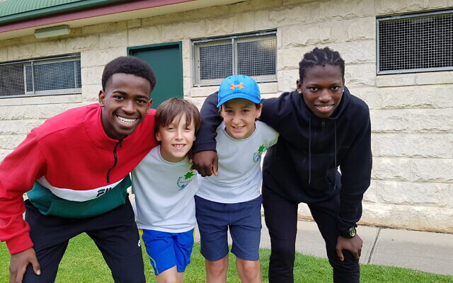 Maccabi Victoria Tennis Club juniors Jarrod and Joshua Strunin (centre) with Australian-Sudanese participants at an inter-community tennis day.