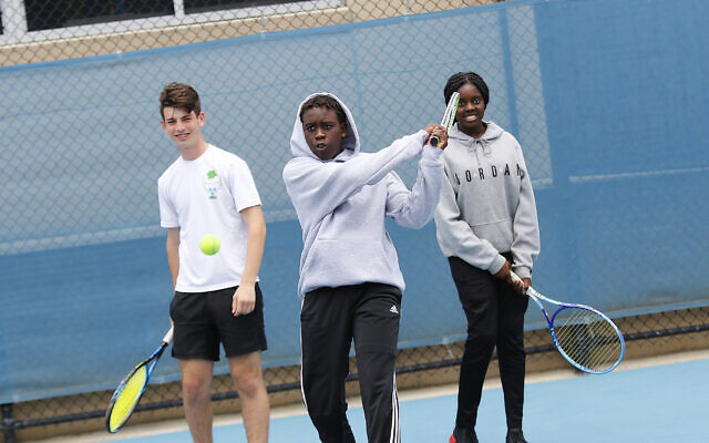 Maccabi tennis junior Brad Lowe (left) with Australian teenagers of Sudanese heritage at an inter-community tennis day organised by Maccabi and the Twentyman Foundation. Photo: Peter Haskin