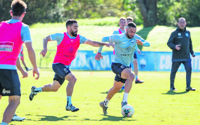 Jordi Swibel dribbles at pace during a recent Sydney FC training session, pursued by teammate Anthony Caceres. Photo: Jaime Castaneda/Sydney FC