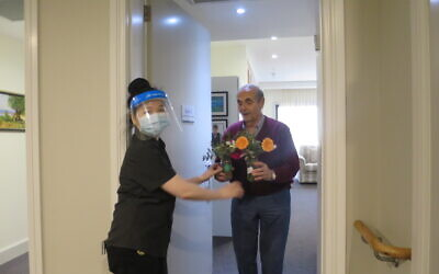 Arcare Caulfield resident Leo Bloumis receives his flowers as a result of the Sponsor a Floral Posy Jar initiative.