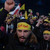 "FILE - In this  Jan. 5, 2020 file photo, supporters of Hezbollah leader Sayyed Hassan Nasrallah chant slogans ahead of the leader's televised speech in a southern suburb of Beirut, Lebanon. The headbands read, ""Death to America."" Twenty years after Hezbollah guerrillas pushed Israel's last troops from southern Lebanon, both sides are gearing up for a war that neither seems to want. Israeli troops are drilling for a possible invasion of Lebanon and striking Hezbollah targets in neighboring Syria. Hezbollah is beefing up its own forces and threatening to invade Israel. (AP Photo/Maya Alleruzzo, File)"