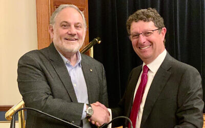 Outgoing president Justice Stephen Rothman congratulates incoming president David Lewis at The Great Synagogue's AGM.