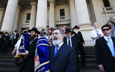 Following a double Torah dedication at Parliament House, Victoria, in 2012, then chief rabbi Lord Jonathan Sacks carries one of the Torahs in a procession to East Melbourne Hebrew Congregation. Photo: Peter Haskin