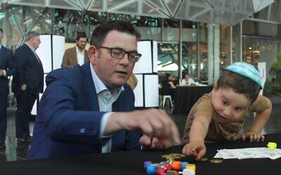 Premier Daniel Andrews playing dreidel with Lev Kaltmann. Photo: Ash Waters