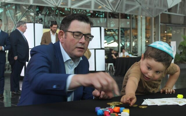 Premier Daniel Andrews playing dreidel with Lev Kaltmann. Photo: Ash Waters