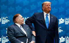 President Donald Trump pats Las Vegas Sands Corporation Chief Executive and Republican mega donor Sheldon Adelson on the arm before speaking at the Israeli American Council National Summit in Hollywood, Fla., Saturday, Dec. 7, 2019. (AP Photo/Patrick Semansky)