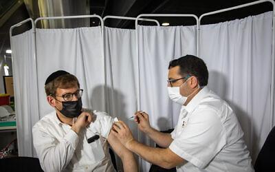 People receives a Covid-19 vaccine injection, at Clalit Covid-19 vaccination center in Jerusalem, on January 28, 2021. Photo by Olivier Fitoussi/Flash90 *** Local Caption ***  נגד נגיף הקורונה ארנה קורונה חיסון מורה חינוך כללית אזרחים חיסונים