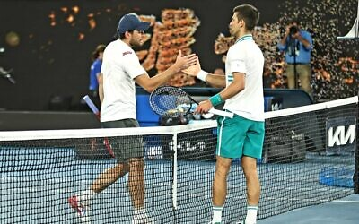 Aslan Karatsev shakes hands with Novak Djokovic at the Australian Open semi-final on Thursday night. Photo: Peter Haskin