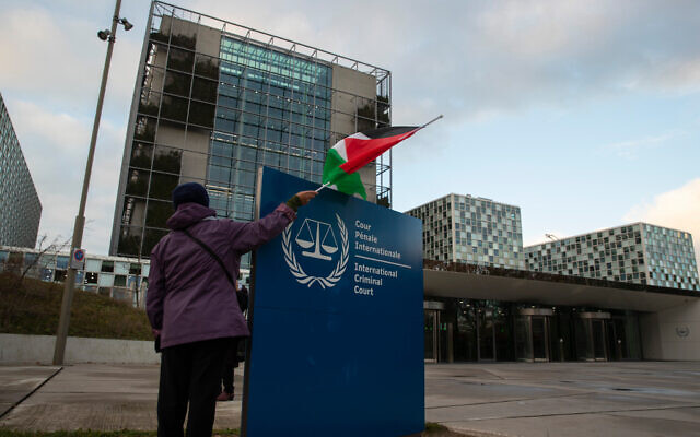 A demonstrators poses with a Palestinian flag outside the International Criminal Court, ICC, during rally urging the court to prosecute Israel's army for war crimes in The Hague, Netherlands, Friday, Nov. 29, 2019. The ICC prosecutor was directed to reconsider her decision to not pursue charges in the Gaza Freedom Flotilla case. (AP Photo/Peter Dejong)