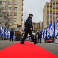 "A Kosovo police officer walks across a red carpet prior to a ceremony held digitally, in the capital Pristina, Monday, Feb. 1, 2021. Kosovo and Israel formally have established diplomatic ties in a ceremony held digitally due to the pandemic lockdown. Kosovo's Foreign Minister Meliza Haradinaj-Stublla and her Israeli counterpart Gabriel Ashkenazi on Monday held a virtual ceremony signing the documents. The two countries considered it as ""making history"" and marking ""a new chapter."" (AP Photo/Visar Kryeziu)"