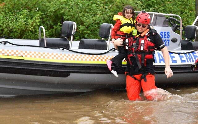 SES assisting a family during their evacuation from a flooded property at Upper Colo in north-western Sydney this week. Photo: AAP Image/Dean Lewins