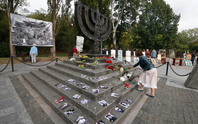 A woman lays flowers at a menorah monument close to the Babi Yar ravine where tens of thousands of Jews were killed during WWII. Photo: AP Photo/Efrem Lukatsky