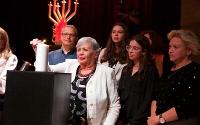 Sofia Parij lights a candle with her family. Photo: Giselle Haber