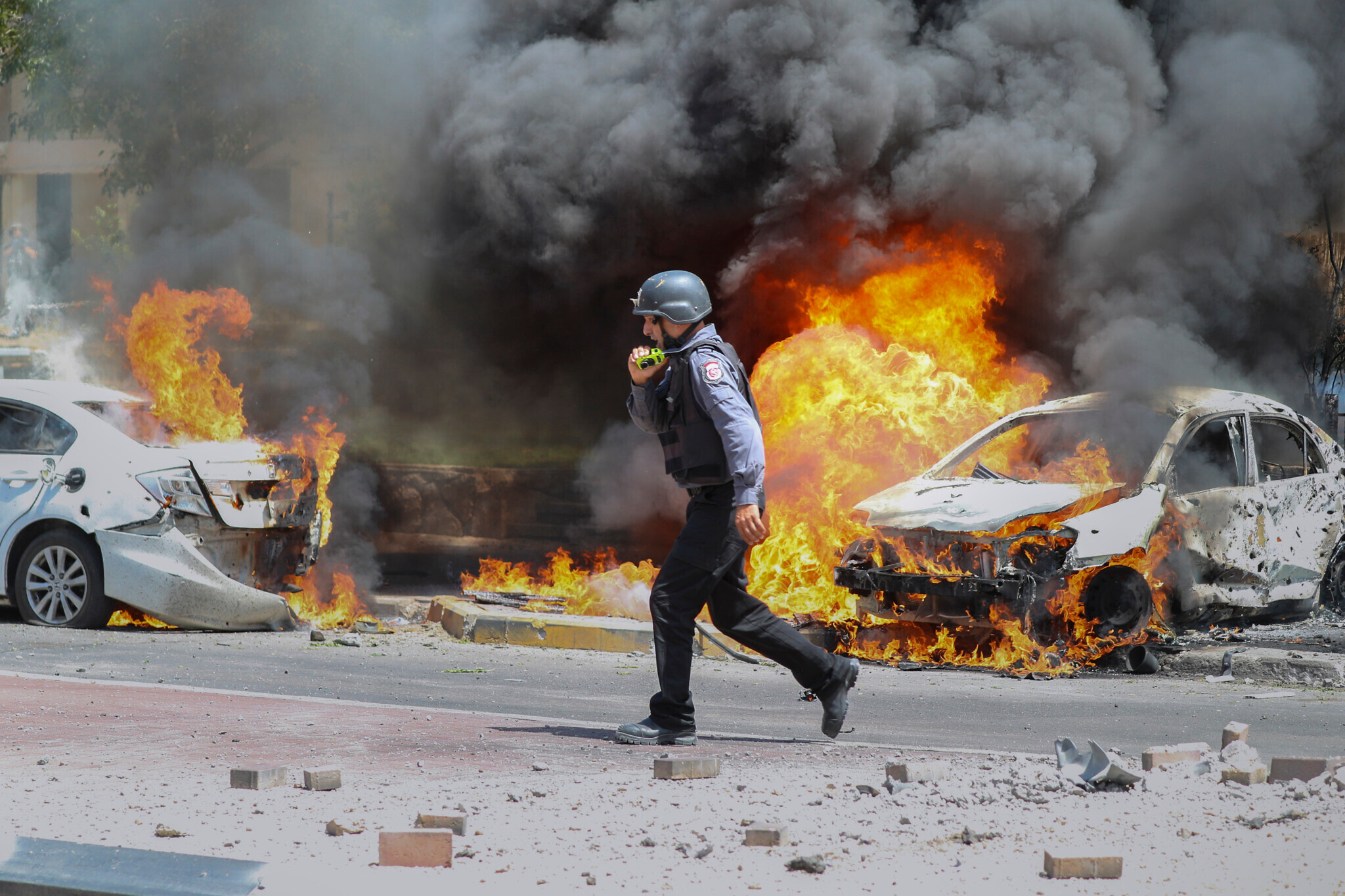 An Israeli firefighter in Ashkelon walks next to cars hit by a missile fired from the Gaza Strip on Tuesday. Photo: AP Photo/Ariel Schalit