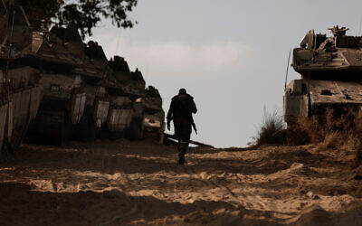 An Israeli soldier walks at a staging ground near the border with the Gaza Strip, in southern Israel, May 20, 2021. (AP Photo/Maya Alleruzzo)