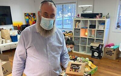 Jewish House CEO Rabbi Mendel Kastel with client food packs.
