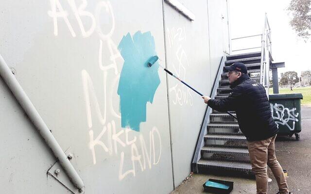 AJAX Football Club president Ronnie Lewis removing the graffiti on Sunday. Photo: Peter Haskin