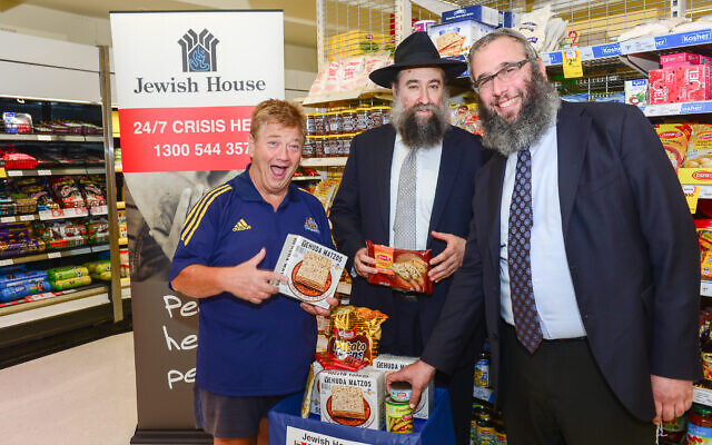 Jonathan Coleman (left) with Rabbi Nochum Schapiro and Rabbi Mendel Kastel helping with Jewish House's Pesach food drive. Photo: Henry Benjamin