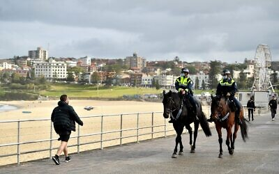 Mounted police on patrol at a deserted Bondi Beach as The AJN's Evan Zlatkis walks past.Photo: AAP Image/Joel Carrett