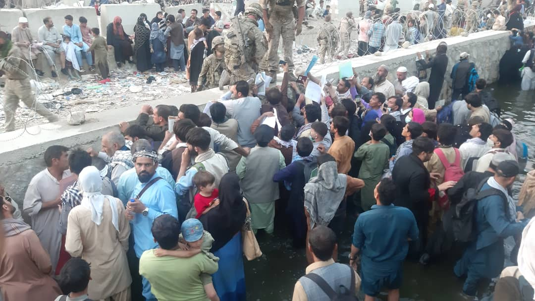 Afghans standing in a canal outside of Kabul airport, waiting to be accepted into the queue by allied troops.