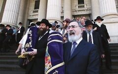 Rabbi Jonathan Sacks and Rabbi Dovid Gutnick (left) lead a procession from Parliament to East Melbourne Shule, following a double Torah dedication in 2012. Photo: Peter Haskin