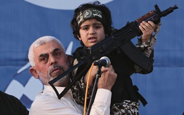 Hamas leader Yahya Sinwar holds the child of an Al-Qassam Brigades fighter, killed in the May conflict with Israel, during a rally in Gaza.  Photo: Emmanuel Dunand/AFP