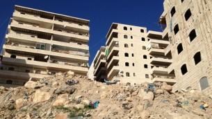 تلة من القمامة وبقايا ادوات البناء بجانب حي سكني في رأس خميس 16 يناير 2014 (بعدسة الحانان ميلر/ تايمز اوف اسرائيل)