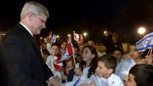 اطفال مع اعلام اسرائيلية وكندية يرحبون برئيس الوزراء الكندي ستيفان هاربر 2014 (بعدسة حاييم زاخ/ فلاش 90)