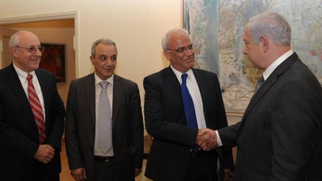 رئيس الوزراء بنيامين نتنياهو يصافح صائب عريقات في القدس 2012 على اليسار يقف مساعد نتانياهو يتسحاق مولوكو (Amos Ben Gershom/GPO/Flash90)