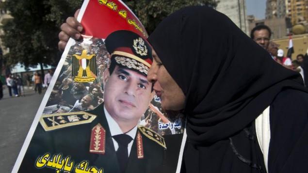 سيدة مصرية تقبل صورة السيسي في ميدان التحرير 6 اوكتوبر 2013 (أرشيف خالد دسوقي أ ف ب)