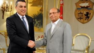 الرئيس التونسي المنصف المرزوقي (يمين) مصافحا رئيس الوزراء مهدي جمعة في قرطاج 26 يناير 2014 (فتحي بلعيد/ أ ف ب)