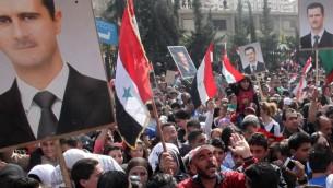 دمشق سوريا, سوريون يرفعون العلم السوري وصور بشار الاسد في مظاهرة لتأييد النظام في حي دومار (أ ف ب)
