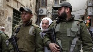 رجل فلسطيني يقف وراء قوات الامن الاسرائيلية في زقاق متجه الى مسجد الاقصى في القدس الشرقية 25 فبراير 2014 (أ ف ب)